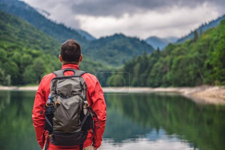 Hiker standing by the mountain lake