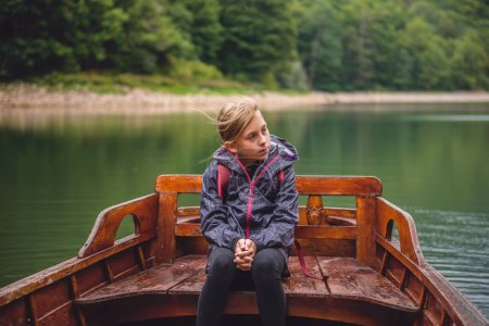 girl sitting in wooden boat