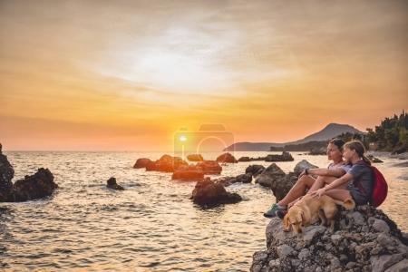 Photo pour Mère et fille avec un petit chien jaune marchant le long du littoral au coucher du soleil - image libre de droit