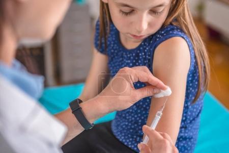 female giving girl vaccine shot
