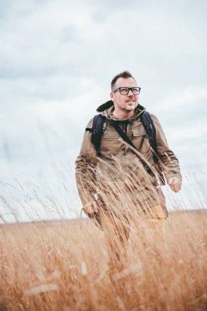 Hiker walking in high grass
