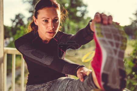 woman doing stretching on city bridge