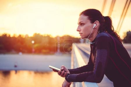 Photo for Fitness woman using smart phone and resting after running - Royalty Free Image