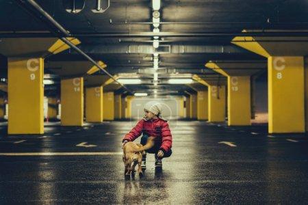 Girl with dog in public garage