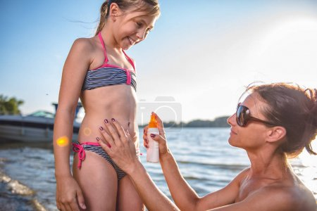 Mother applying sun protection cream