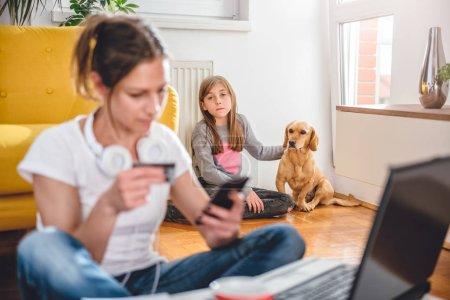 Photo pour La fille solitaire et triste assis avec chien et chercher l'attention alors que mère magasinage en ligne et à l'aide de téléphone intelligent - image libre de droit