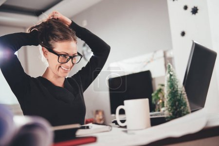 Woman stretching her back at desk in home office