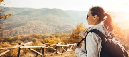 Woman enjoying view on top of mountain during sunset