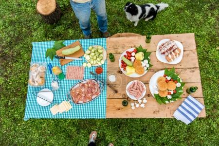 Wooden table with food and drink ready for barbecue party