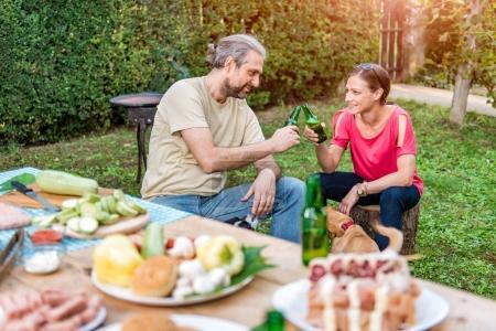 Photo pour Couple faisant un toast avec de la bière sur barbecue fête à la maison - image libre de droit
