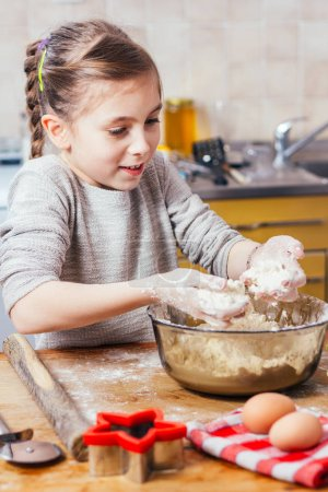 little girl making dough at home kitchen