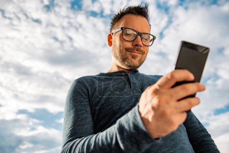Man with glasses using smart phone outdoor. He is wearing blue shirt.