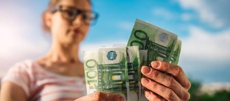 Woman with glasses holing money in her hand. She is holding European currency.