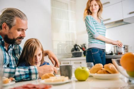 Father and daughter using tablet in the kitchen during breakfast while mother happily watching them.