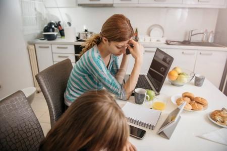 Photo pour Inquiète mère travaillant à la maison dans la cuisine avec sa fille - image libre de droit