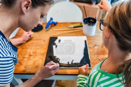 Art teacher helping a student with her painting during art class