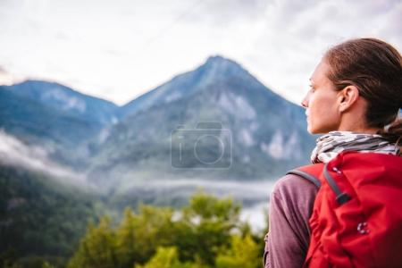 Woman with red backpack standing on mountain and looking sideways
