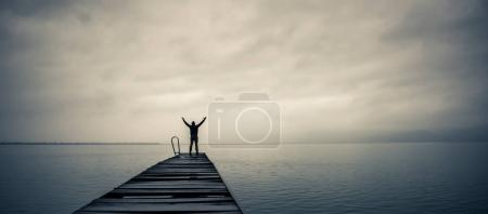 Man standing on a old wooden dock with raised hands and looking at the sky