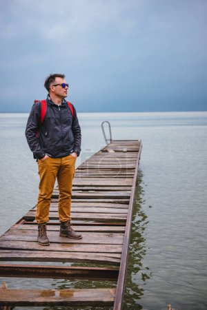 Man standing on wooden dock on stormy weather. He is wearing red backpack, blue jacket and leather boots