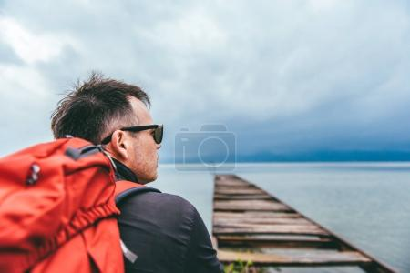 Man standing on a river dock and looking sideways