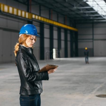 Photo pour Site Inspector, prendre des notes dans le grand hall industriel - image libre de droit