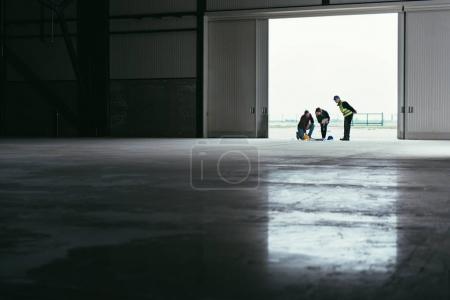 Architect team At Work Site checking Blueprints at big hangar doors