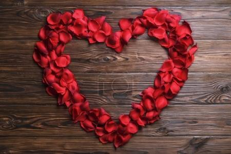 Photo pour Geste romantique, confession d'amour, bonne Saint-Valentin, carte de vœux anniversaire, invitation de mariage. Coeur en forme de pétales de rose rouge décor, fond texturé en bois foncé. Gros plan, vue du dessus, espace de copie - image libre de droit