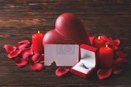 Conceptual photo of wedding or engagement ring with candles in shape of heart. St. Valentine`s day