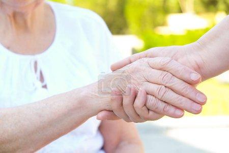 Starych i młodych trzymając ręce na jasnym tle z bliska. Pomocna dłoń, opieka podeszłym wieku pojęcia.
