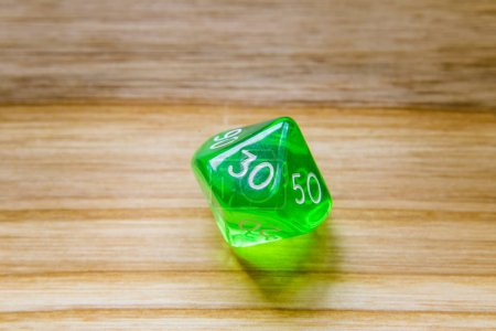 A translucent green ten sided playing dice on a wooden backgroun