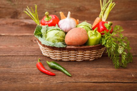 Foto de Verduras frescas en una cesta sobre un fondo de madera. Col, pimiento, patatas, ajo, cebolla, Chile y zanahoria. De la cosecha. Día de acción de gracias. Espacio para texto. - Imagen libre de derechos