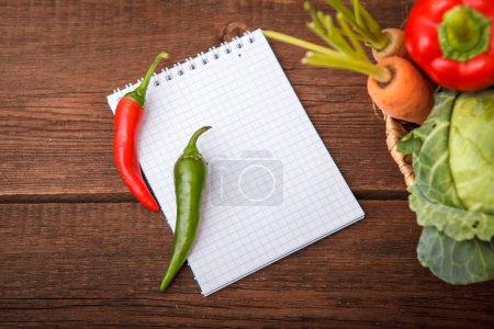 Foto de Una hoja de papel con vegetales sobre un fondo de madera. Cesta con pimienta, repollo de col, patatas, ajo y zanahorias. De la cosecha. Concepto de otoño. Espacio para texto. - Imagen libre de derechos