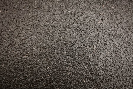 Black asphalt road with a beautiful texture. Fresh and hot asphalt. The asphalt in the morning or afternoon