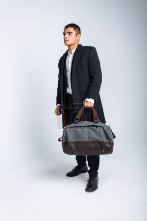 Stylish man in Studio on a white background, with a bag for travel, isolated, background, man goes on a journey