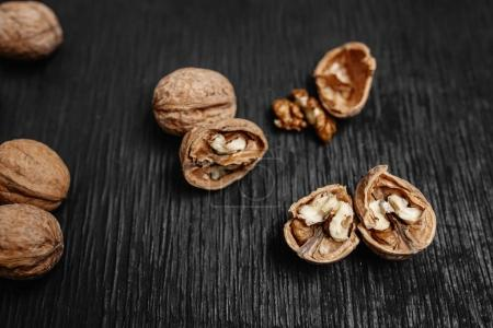 Lots of fresh nuts on a black wooden background. Best practices for designer