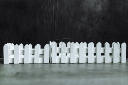 Black background. A white picket fence.