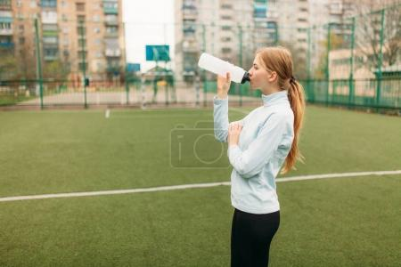 Girl after exercise, drinking water on the football field. Portrait of beautiful girl in sportswear.
