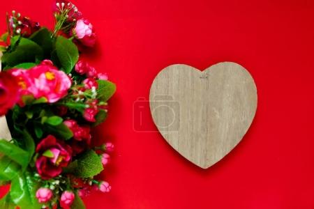 Valentine's day gift for the second half, a bouquet of flowers, a romantic photo, a wooden heart on a red background, background suitable for advertisement , insert text