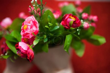 Valentine's day,florist woman packs a bouquet of flowers of roses in a paper wrapper with a bow on wooden table, suitable for advertisement,