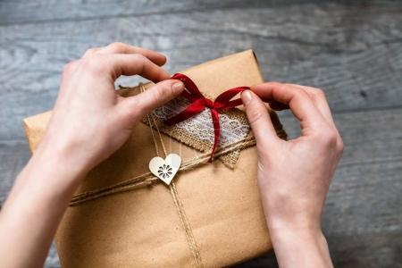 Female hand holding a wrapped gift ,Valentine's Day, romantic photo . Romantic grey wooden background with hearts and gifts, suitable for advertising