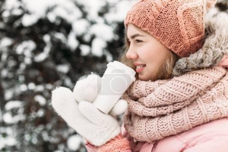Portrait of a beautiful young girl in white knitted mittens, outdoors, drinking a hot beverage , bright winter day.woman smiling and happy, macro, trees, first snow.