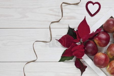 Red apples, poinsettia and Christmas spices on white wooden background, top view