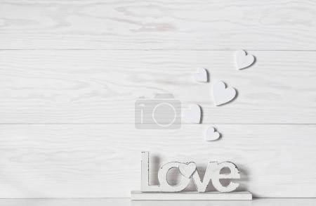 Photo pour Gros plan de Différentes tailles de cœurs et d'amour figure sur fond blanc en bois. Saint Valentin - image libre de droit