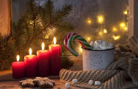 close-up of hot mug with marshmallow and candy canes with red candles, Christmas decor on festive background. Christmas concept.