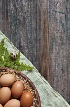close-up of fresh homemade eggs on plate with green leaves on wooden table.