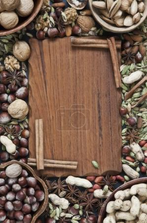 close-up of wooden board with nuts and spices frame