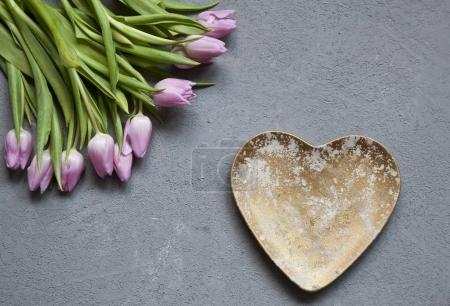 close-up of beautiful pink tulips flowers with heart on wooden table background