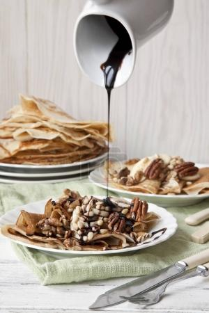 Close-up of Traditional homemade pancakes with nuts and chocolate on white vintage wooden background. Celebration of Maslenitsa