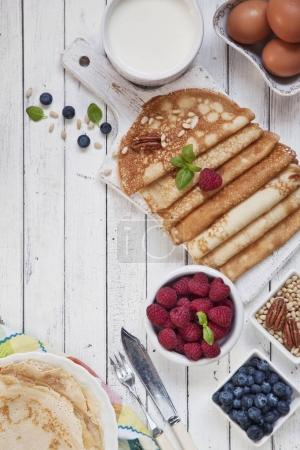 Close-up of Traditional homemade pancakes with berries on white vintage wooden background. Celebration of Maslenitsa