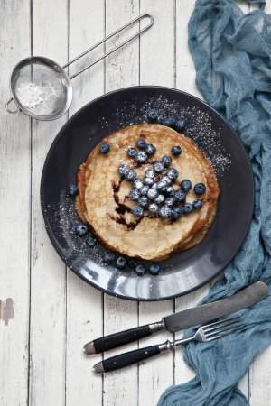 Close-up of Traditional homemade pancakes in black plate on white vintage wooden background. Celebration of Maslenitsa